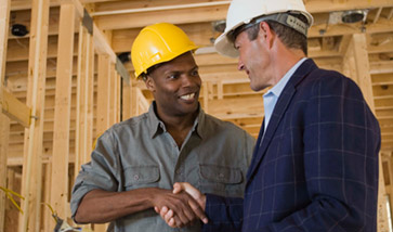men in hard hats shaking hands